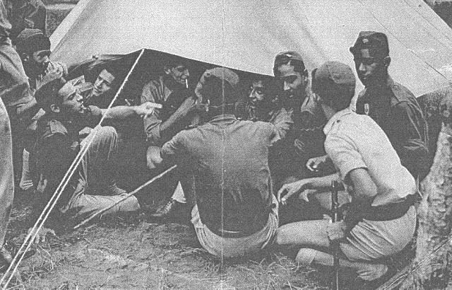 1953 - Acampamento da Milícia da Mocidade Portuguesa. Por baixo da lona, estou eu de cigarro na boca e o Paraíso Pinto. Fora, à esquerda da foto, reconheço o Amaral Leitão