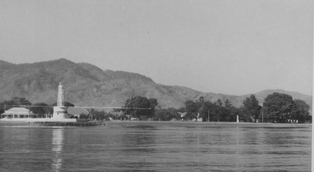 Farol do porto de Díli, à esquerda e Bairro do Farol, à direita, onde se vê a enorme e frondosa árvore que ainda existe.